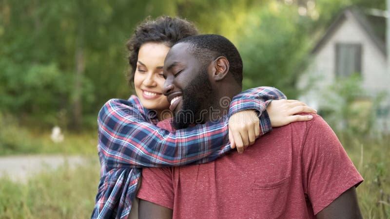 Uśmiechający się niedawno pary małżeńskiej świętuje kupujący nową chałupę w wsi fotografia stock