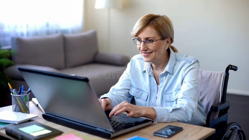 Uśmiechający się niepełnosprawnego starszego damy gawędzenie w ogólnospołecznej sieci, dostaje obeznany online zdjęcia stock