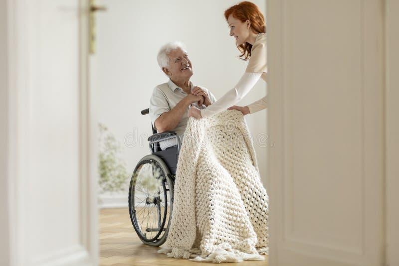 Uśmiechający się obezwładniającego mężczyzna w życzliwym wolontariuszie i wózku inwalidzkim wewnątrz zdjęcie stock