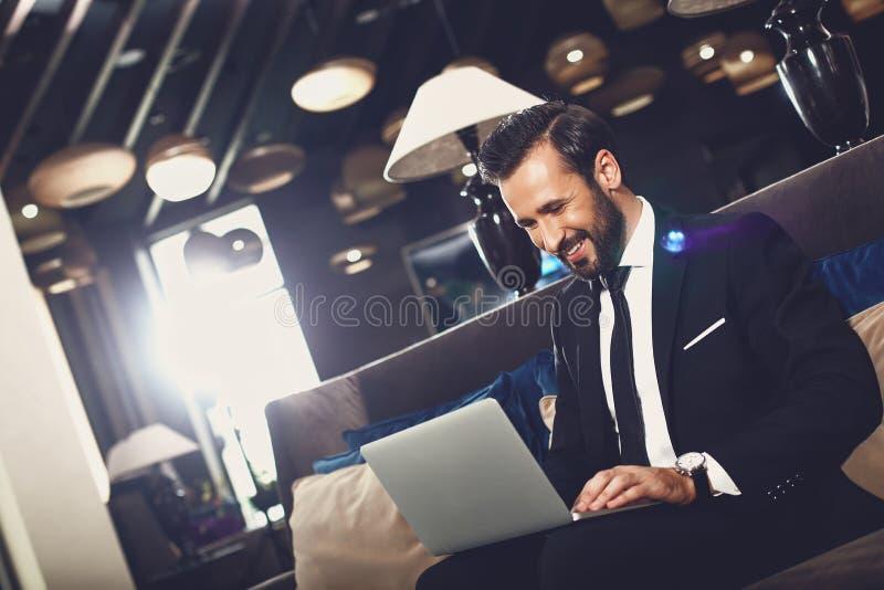 Uśmiechający się przystojny mężczyzna siedzący z laptopem fotografia stock