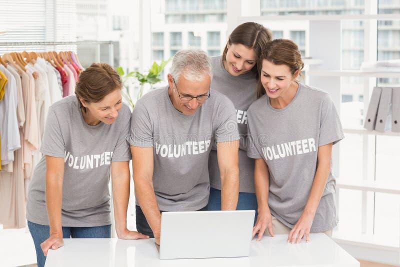 Uśmiechający się wolontariuszów używa laptop wpólnie fotografia royalty free