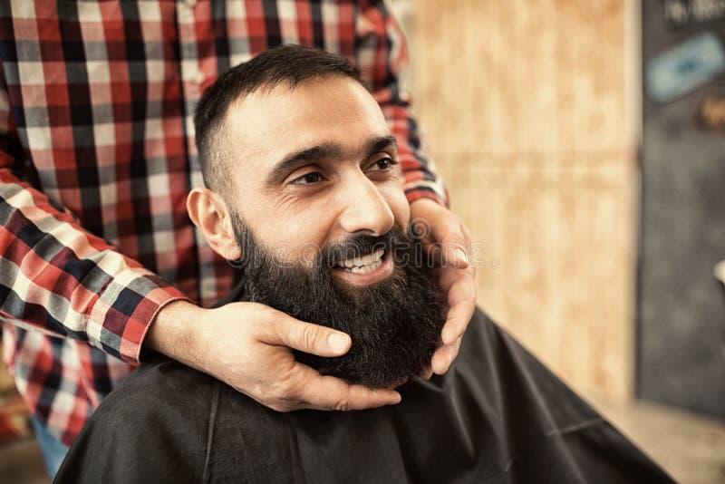 Uśmiechający się zadowolonego modnisia klienta odwiedza fryzjera męskiego sklep, patrzeje g zdjęcia stock