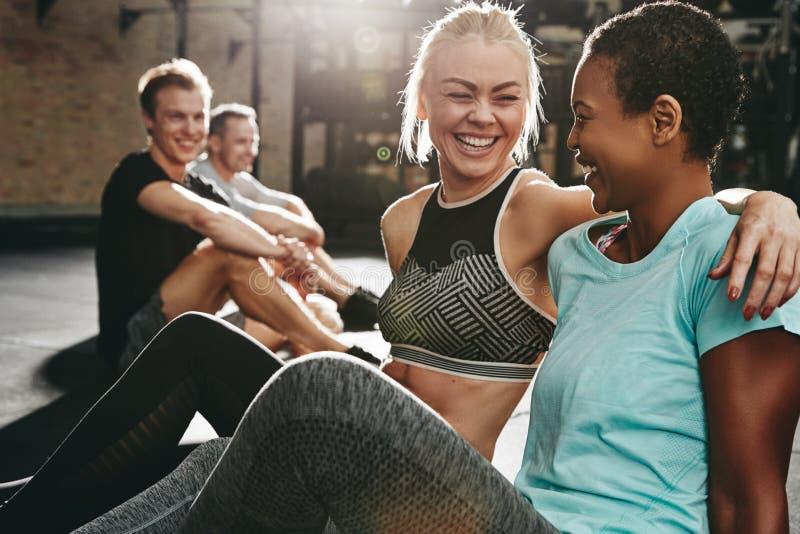 Uśmiechnięci żeńscy przyjaciele śmia się wpólnie po gym klasy fotografia stock