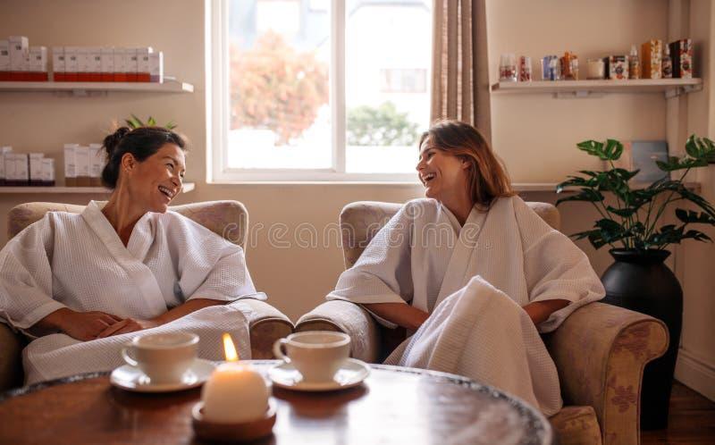 Uśmiechnięci żeńscy przyjaciele czeka w zdroju recepcyjnym terenie zdjęcie stock