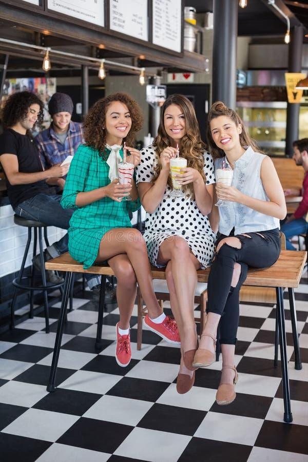 Uśmiechnięci żeńscy przyjaciele pozuje z smoothies przy restauracją obraz stock