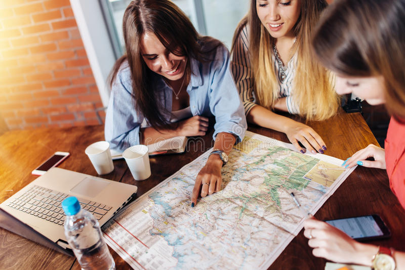 Uśmiechnięci żeńscy przyjaciele siedzi przy biurkiem planuje ich wakacje patrzeje dla miejsc przeznaczenia na mapie fotografia stock