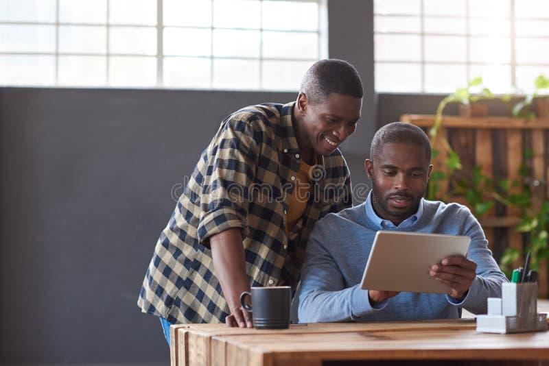 Uśmiechnięci Afrykańscy coworkers używa cyfrową pastylkę w biurze obrazy royalty free