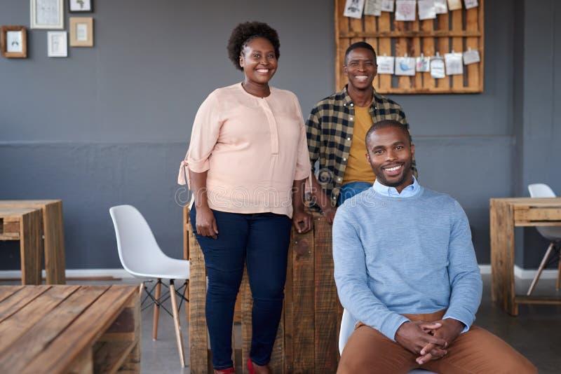 Uśmiechnięci Afrykańscy koledzy pracuje wpólnie w nowożytnym biurze fotografia stock