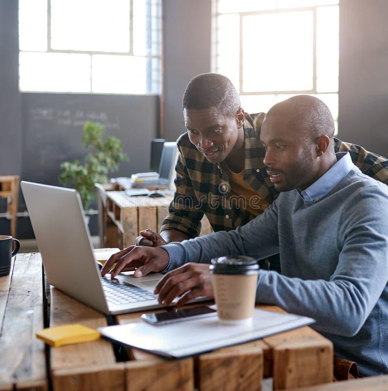 Uśmiechnięci Afrykańscy koledzy używa laptop wpólnie w biurze zdjęcie royalty free