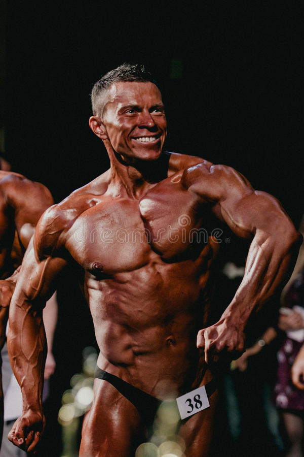 Uśmiechnięci atlet bodybuilders cedzą twój prasy i klatkę piersiową zdjęcia stock