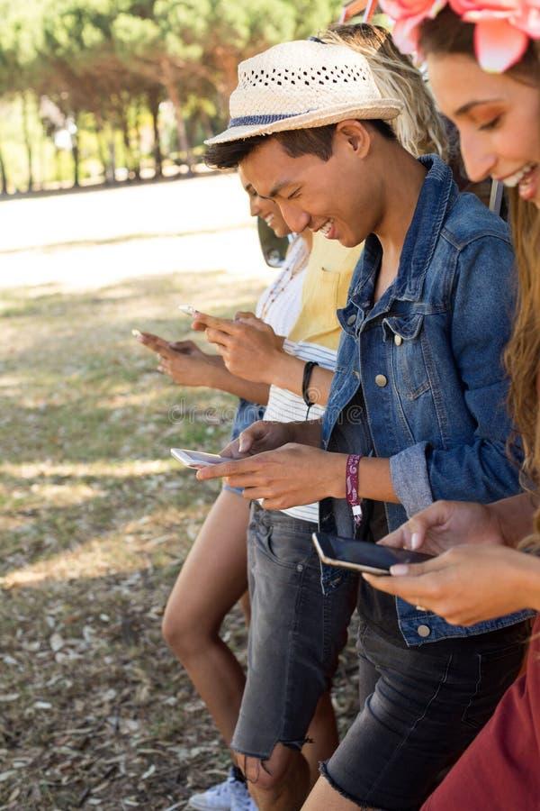 Uśmiechnięci belzebuby używa telefon komórkowego podczas gdy stojący obozowicza samochodem dostawczym fotografia royalty free
