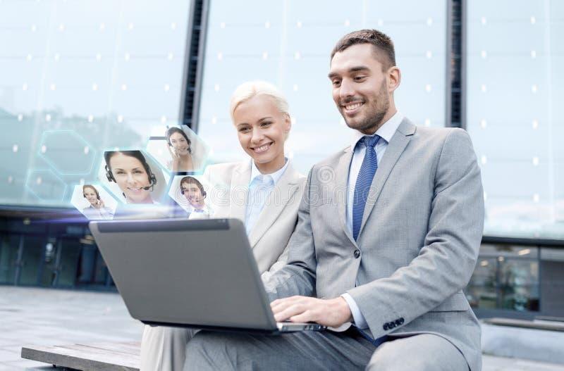 Uśmiechnięci biznesmeni z laptopem outdoors zdjęcia stock