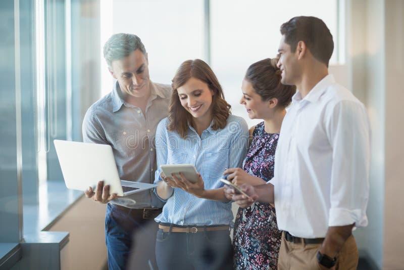 Uśmiechnięci biznesowi koledzy używa telefon komórkowego, cyfrową pastylkę i laptop, obrazy stock