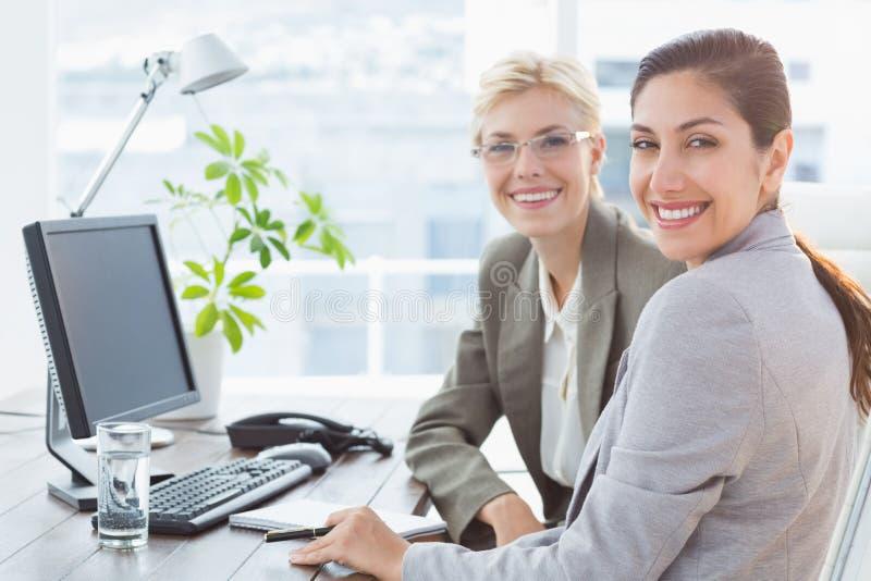 Uśmiechnięci bizneswomany patrzeje kamerę i działanie wpólnie obraz stock
