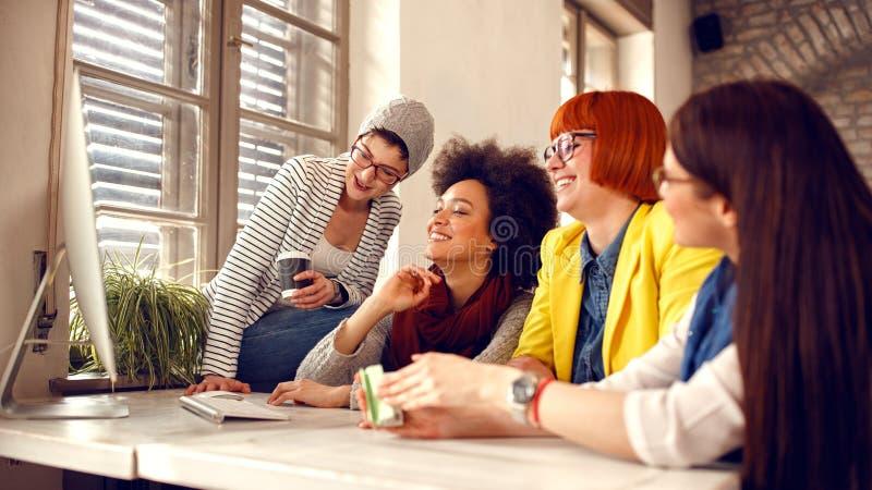 Uśmiechnięci bizneswomany pracuje wpólnie na komputerze zdjęcia stock