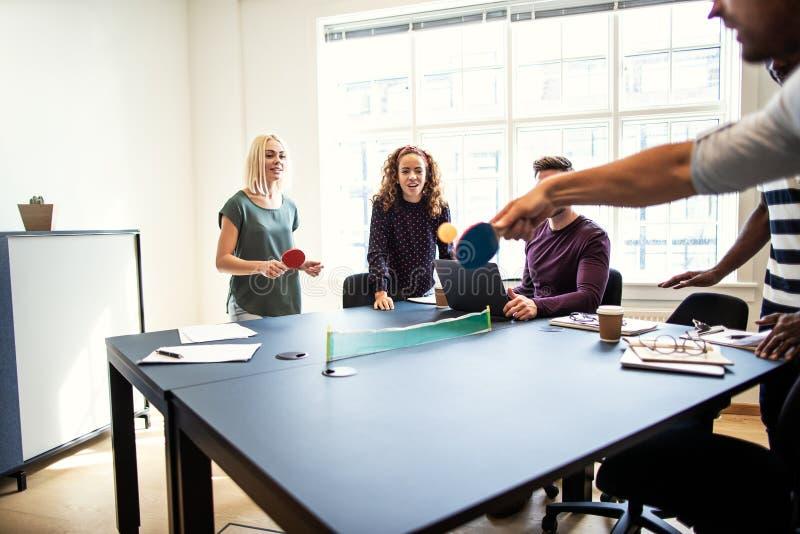 Uśmiechnięci coworkers bawić się stołowego tenisa podczas przerwy od pracy fotografia stock
