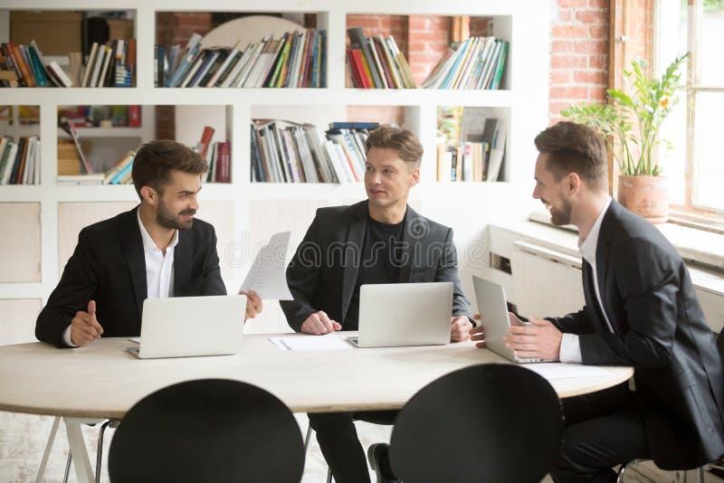 Uśmiechnięci coworkers dyskutuje pozytywne biznesowe sprawy podczas br obraz stock