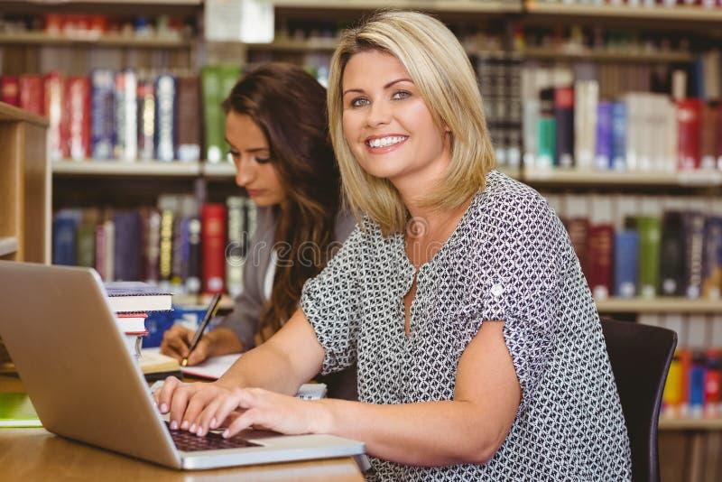 Uśmiechnięci dojrzali żeńscy ucznie używa jej laptop fotografia royalty free