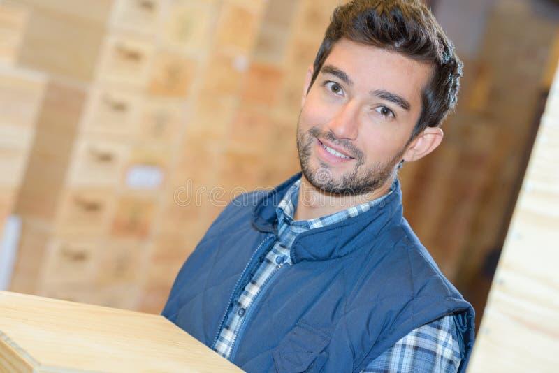 Uśmiechnięci doręczeniowego mężczyzna przewożenia pudełka w magazynie zdjęcia royalty free