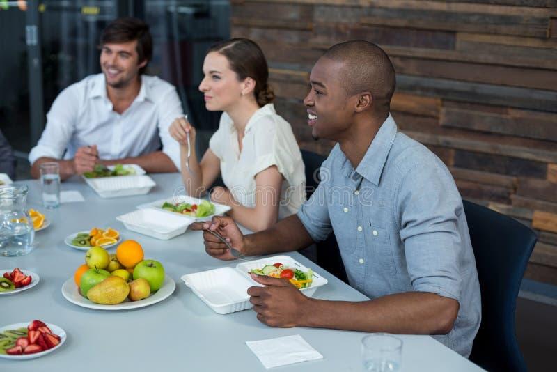 Uśmiechnięci dyrektory wykonawczy ma posiłek w biurze obraz royalty free