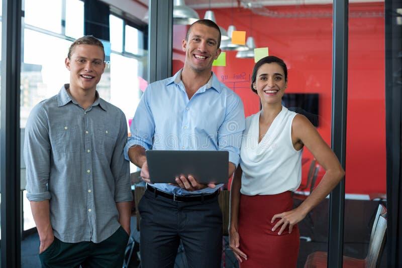 Uśmiechnięci dyrektory wykonawczy stoi w biurze z laptopem zdjęcie stock