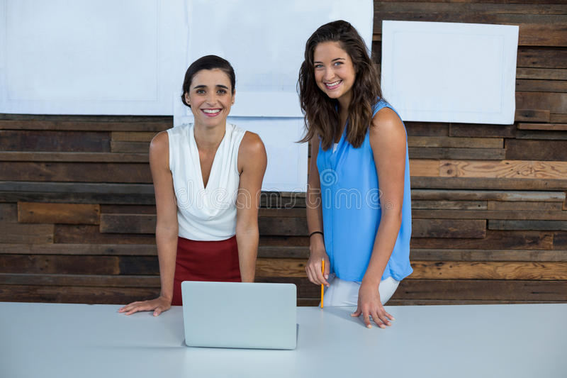 Uśmiechnięci dyrektory wykonawczy stoi w biurze z laptopem na stole zdjęcie stock