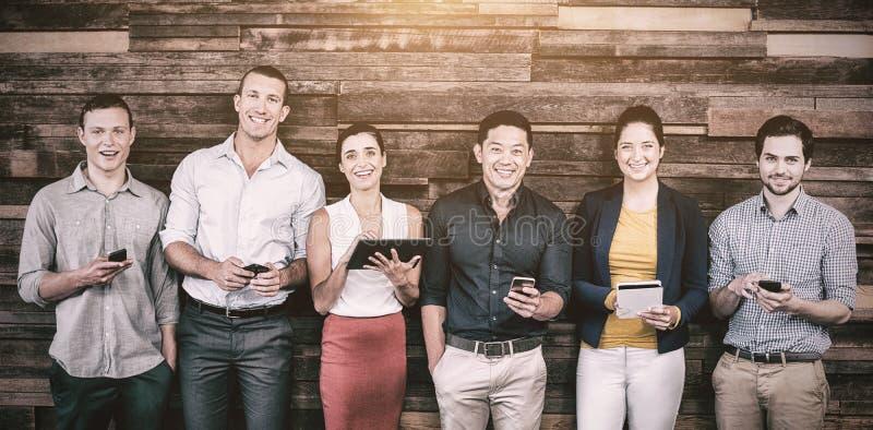Uśmiechnięci dyrektory wykonawczy używa telefon komórkowego i cyfrową pastylkę zdjęcia royalty free
