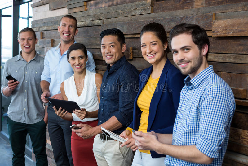 Uśmiechnięci dyrektory wykonawczy używa telefon komórkowego i cyfrową pastylkę w biurze zdjęcia stock