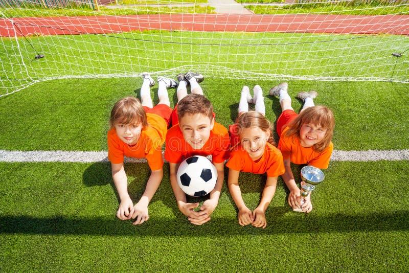 Uśmiechnięci dzieci kłaść na trawie z złotą czara obrazy royalty free