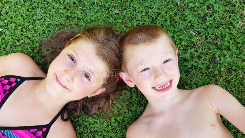 Uśmiechnięci dzieci kłaść na zielonej trawie Poj?cie relaksuje obraz stock