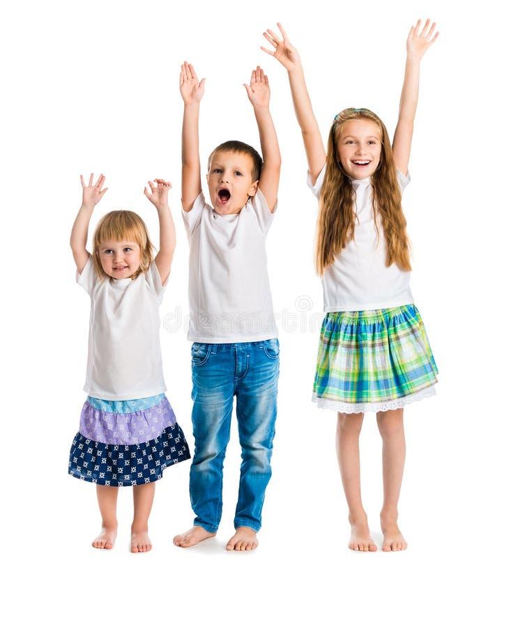 Uśmiechnięci dzieci z rękami up zdjęcia stock