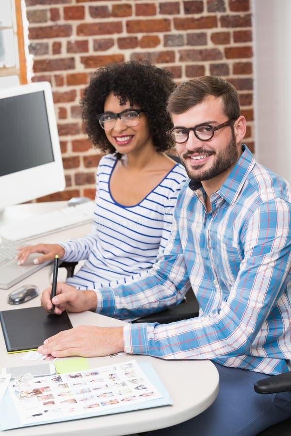 Uśmiechnięci fotografia redaktorzy używa digitizer w biurze zdjęcia royalty free