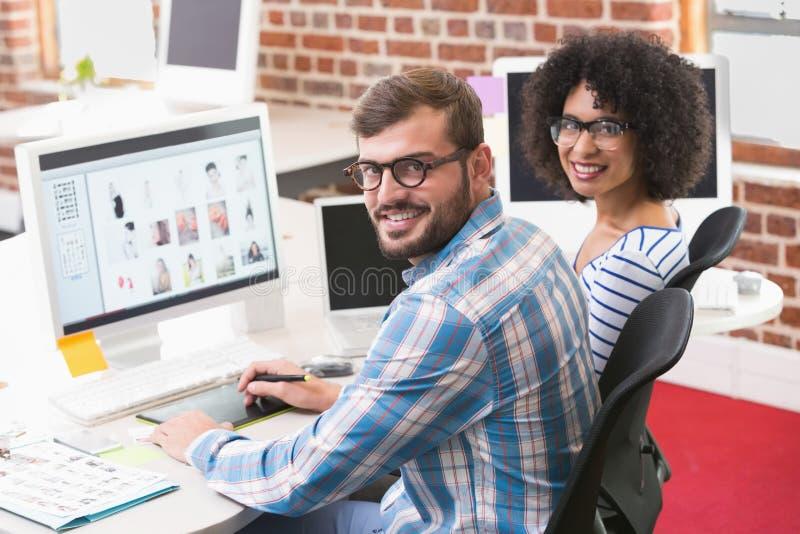 Uśmiechnięci fotografia redaktorzy używa digitizer w biurze obrazy royalty free