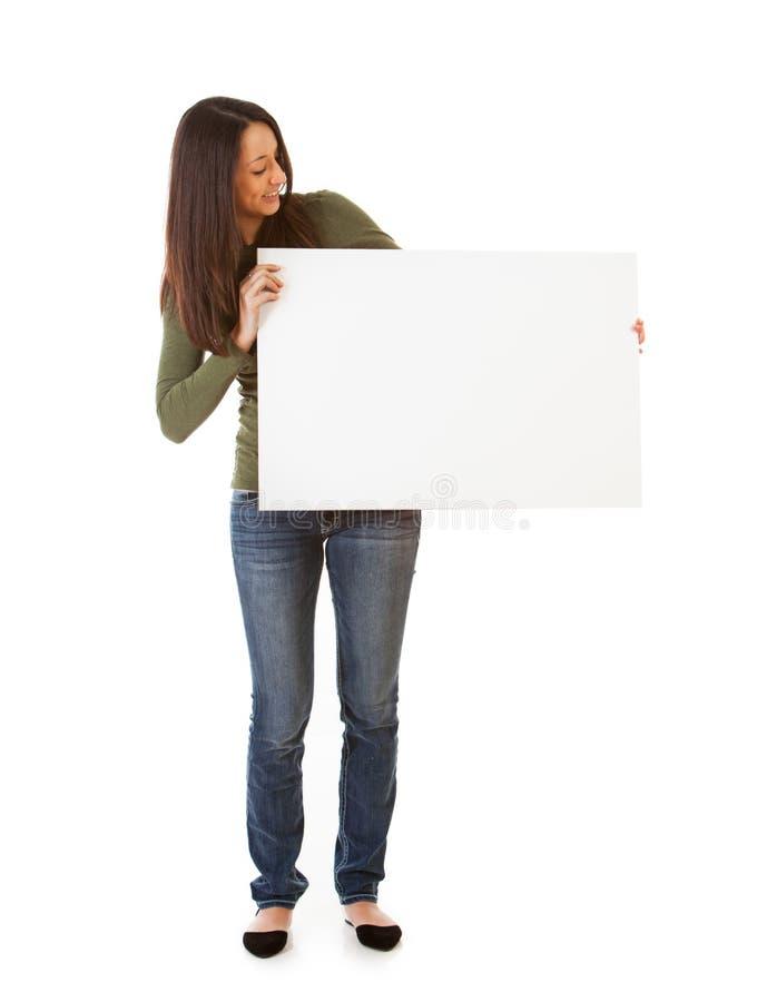 Uśmiechnięci kobiet spojrzenia Przy Pustą plakat deską obraz stock