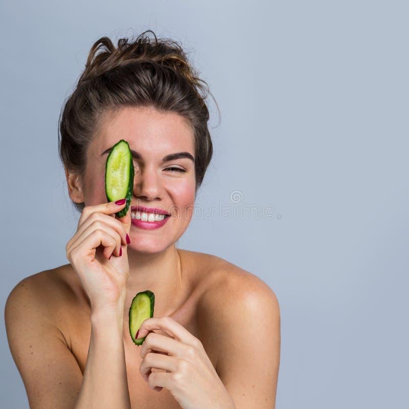 Uśmiechnięci kobiety mienia ogórka plasterki zdjęcie stock