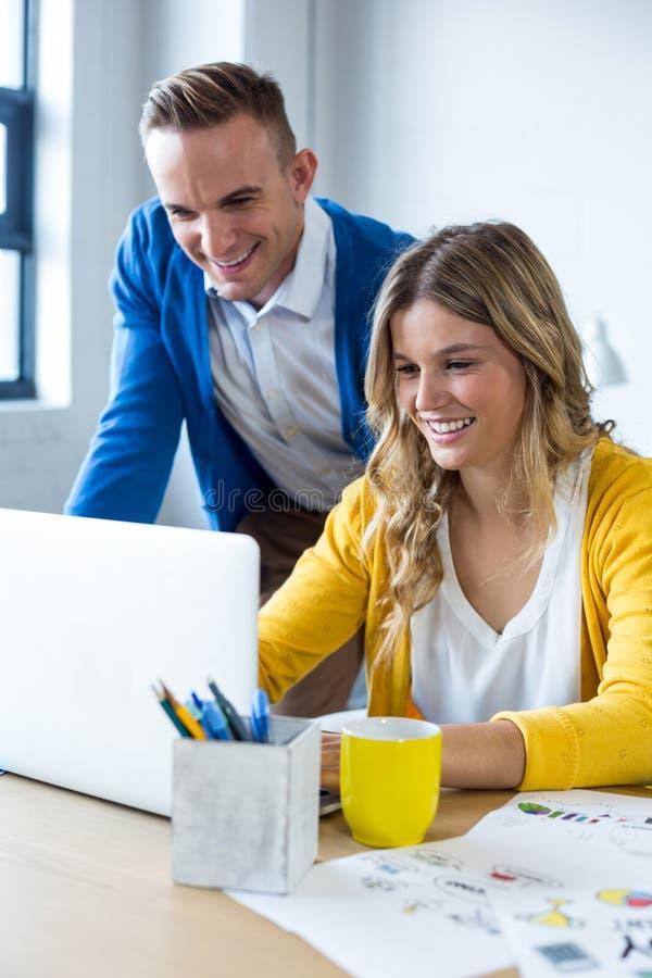 Uśmiechnięci koledzy Używa laptop W biurze fotografia stock
