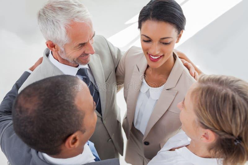 Uśmiechnięci ludzie biznesu obejmuje wpólnie obraz royalty free