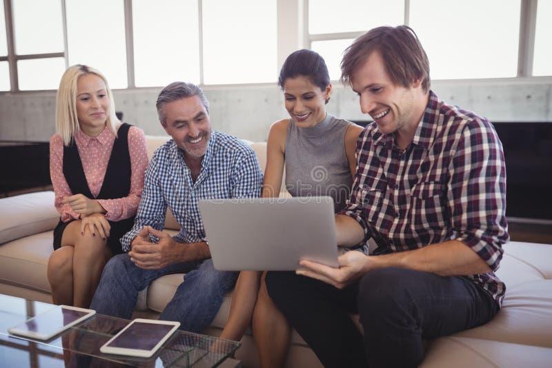 Uśmiechnięci ludzie biznesu pracuje na laptopie przy biurem zdjęcie stock