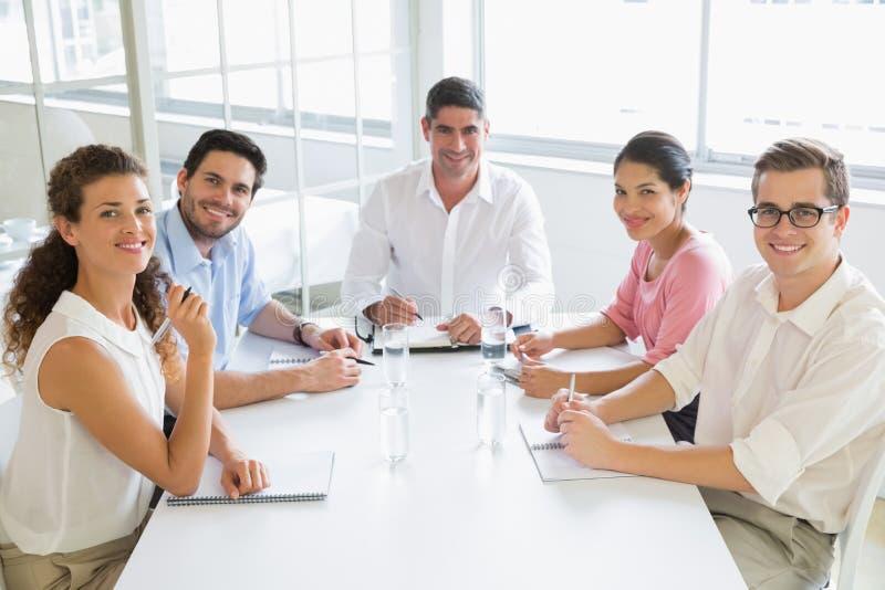 Uśmiechnięci ludzie biznesu przy konferencyjnym stołem obrazy royalty free