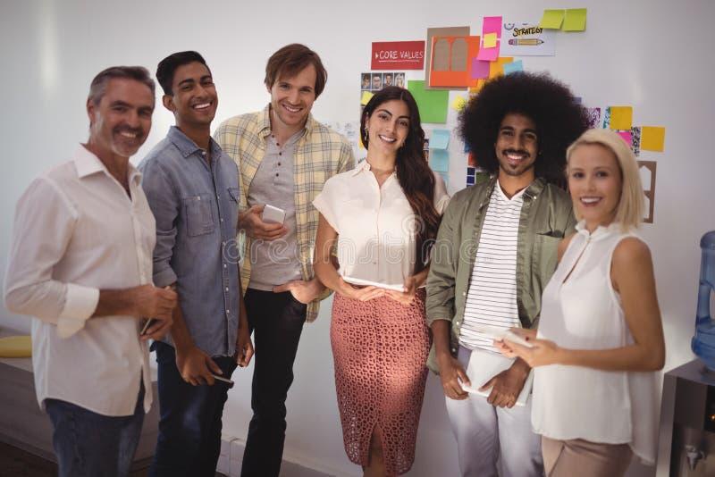 Uśmiechnięci ludzie biznesu stoi w kreatywnie biurze fotografia stock