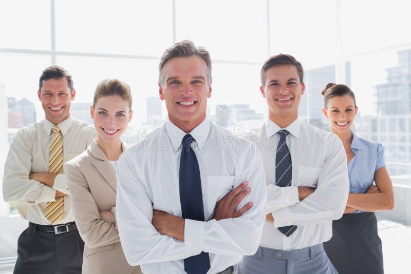 Uśmiechnięci ludzie biznesu z rękami krzyżowali w ich biurze zdjęcie stock