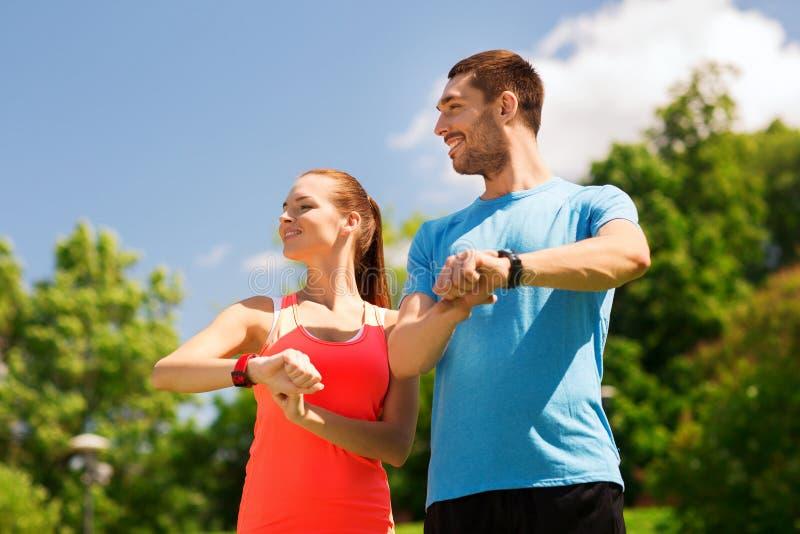 Uśmiechnięci ludzie z tętno zegarkami outdoors obrazy royalty free