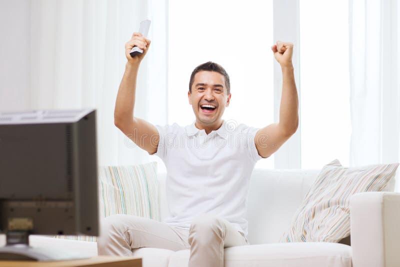 Uśmiechnięci mężczyzna dopatrywania sporty w domu obrazy stock