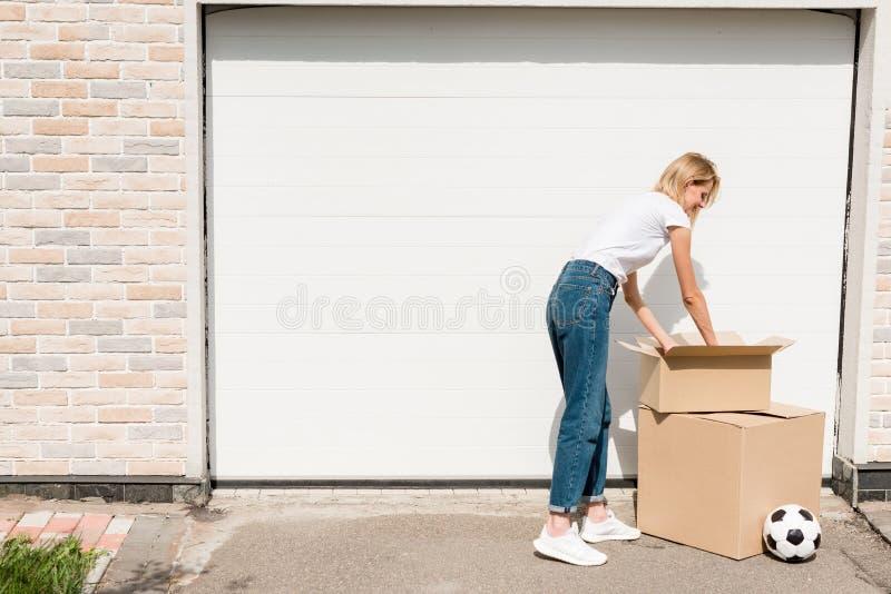 uśmiechnięci młodej kobiety odpakowania kartony blisko piłki nożnej piłki przed garażem nowy obrazy stock