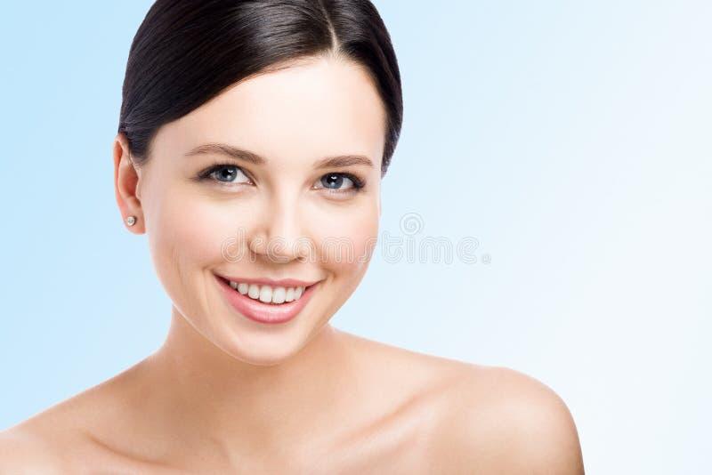 uśmiechnięci młodych kobiet Skóro czyścić skórę rodzaju twarz Zbliżenia piękno na błękicie zdjęcie stock