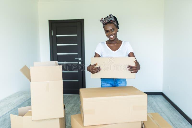 Uśmiechnięta młoda afrykańska kobieta trzymająca kartonowe pudełka z dobytkami, patrząc na kamerę Przejście do nowego mieszkania zdjęcia stock