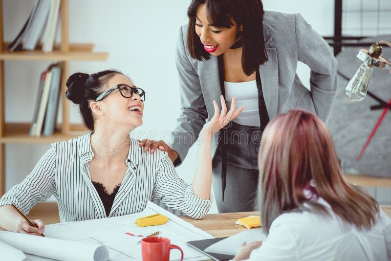 Uśmiechnięci młodzi bizneswomany dyskutuje projekt i działanie z projektem fotografia stock