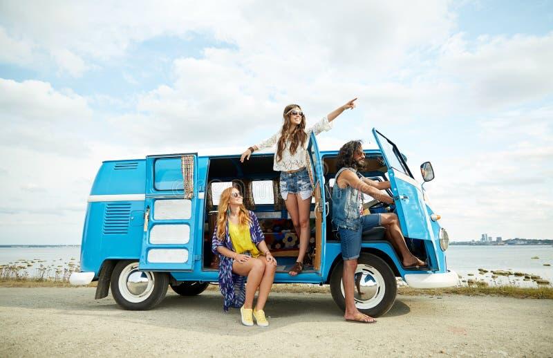 Uśmiechnięci młodzi hipisów przyjaciele nad furgonetka samochodem zdjęcie royalty free