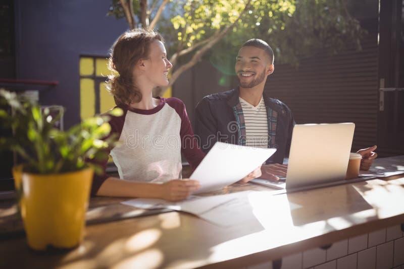 Uśmiechnięci młodzi kreatywnie profesjonaliści opowiada podczas gdy siedzący z laptopem przy sklep z kawą fotografia royalty free