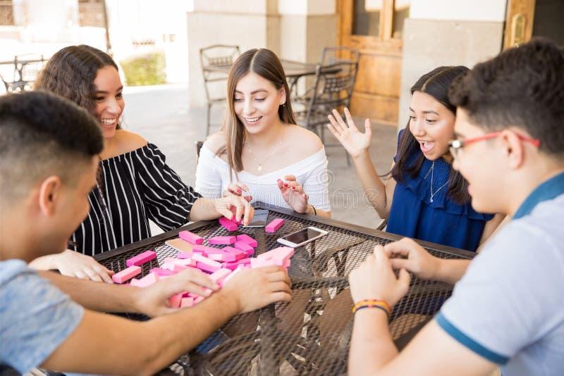 Uśmiechnięci młodzi ludzie bawić się jenga fotografia royalty free